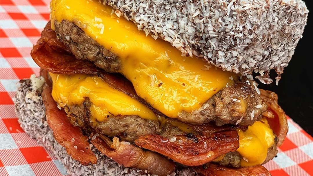 Article heading image for Everybody Stay Calm, A Mammoth Double Patty Cheesy Bacon Lamington Burger Exists
