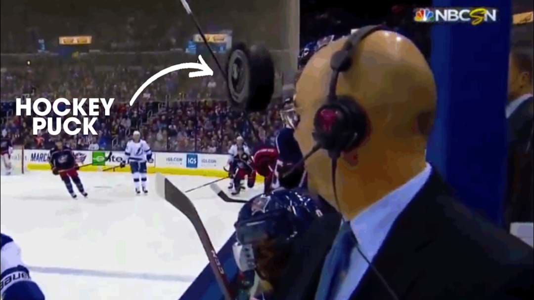 Article heading image for Watch And Whistle Slowly As This Hockey Puck Whizzes Just Centimetres Past A Commentator's Face