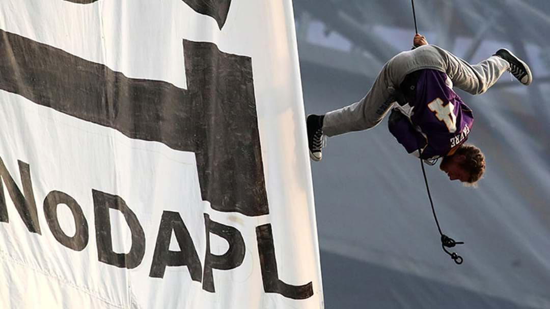 Article heading image for Protestors Hung From The Roof To Unfurl A Huge Banner At An NFL Game This Morning