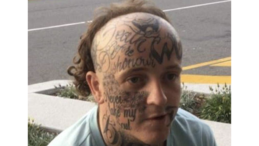 Article heading image for Man With Face Tatts And Cooked Mullet Hunted By Police For Stealing Sex Toys, Cars, A Phone, And Two Lollies